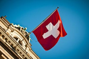 stock-photo-18120052-swiss-flag-waving-on-historic-building